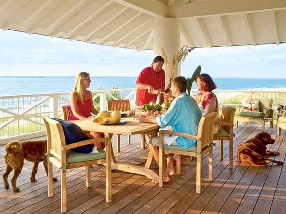 Beachside Covered Porch ~ A simple teak dining table and chairs makes this North Carolina deck the perfect place for a sunset meal. Like a caps visor, the flipped-up roof edge provides extra shade and pushes the rains drop line away from the house.