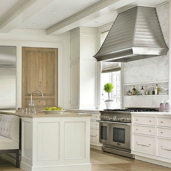 White kitchen beauy! Interior design ideas photo gallery featuring understated kitchen with design by Phoebe Howard for a traditional and classic limestone manor home in Charlotte. Wormy chestnut wood pantry door and glossy white cabinetry mix beautifully. #kitchen #interiordesign #traditional #whitekitchen #classic