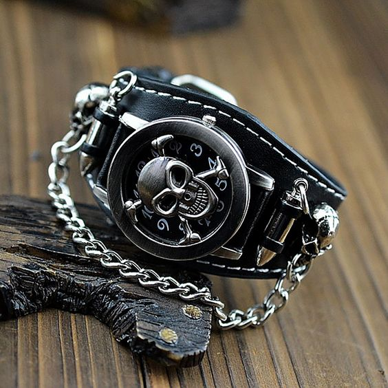 Skulls command respect. Period. This heavy metal skull wristwatch has a metal chain attaching two skulls by their nose ring. The stainless steel case, which opens up to show the full dials, sits betwe