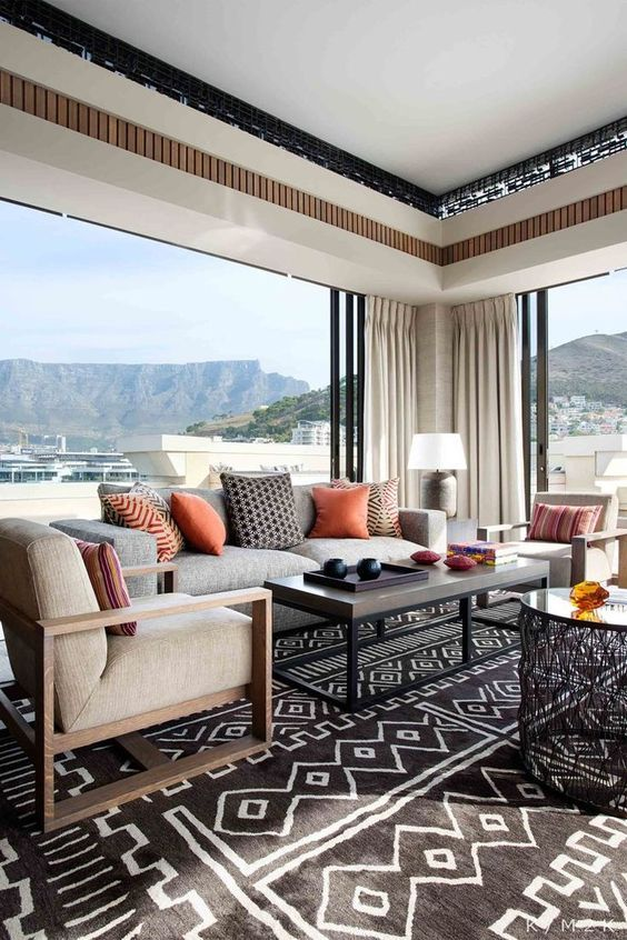 Textiles here create a mood and theme, warm colored pillows and traditional tribal rugs scream Africa