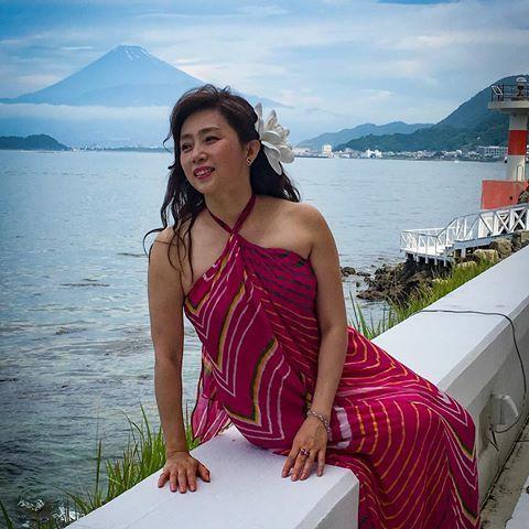 ホルターネックの赤いワンピースを着て座っている藤吉久美子の画像