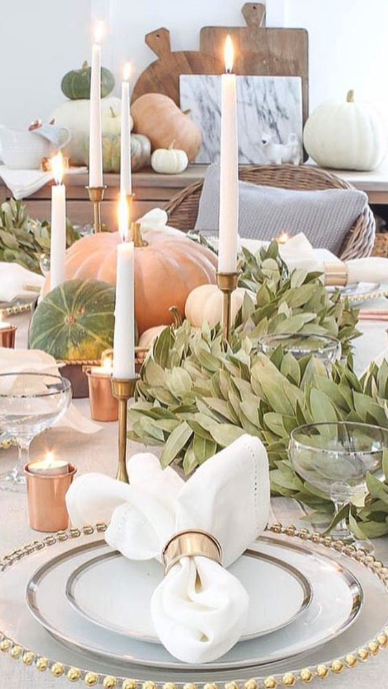 Beautiful thanksgiving table setting in gold and copper. Candles, and pumpkins warm the atmosphere.: