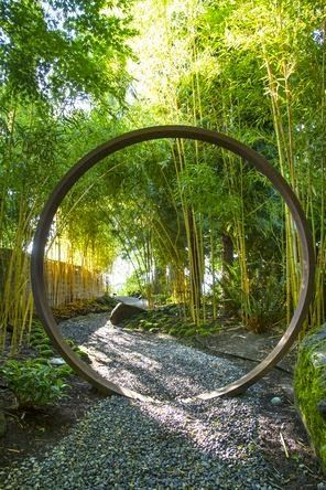 Visitors enter the garden along a shady gravel path, stepping through a moon gate: