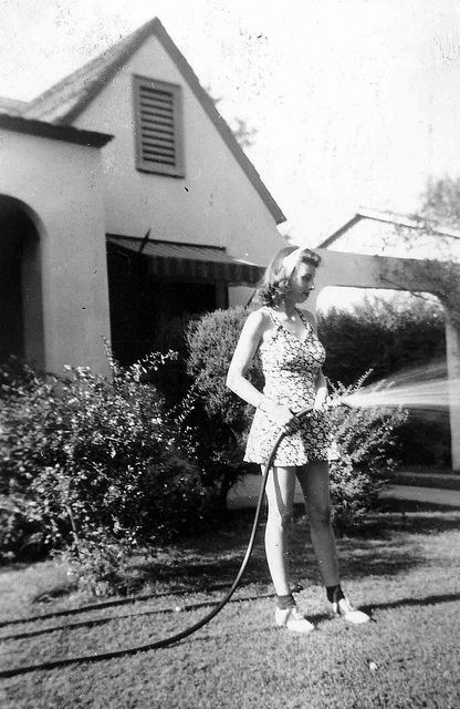 Love her cute hair and printed playsuit, 1942.  Saddle shoes, ankle socks, and garden hose complete the look.