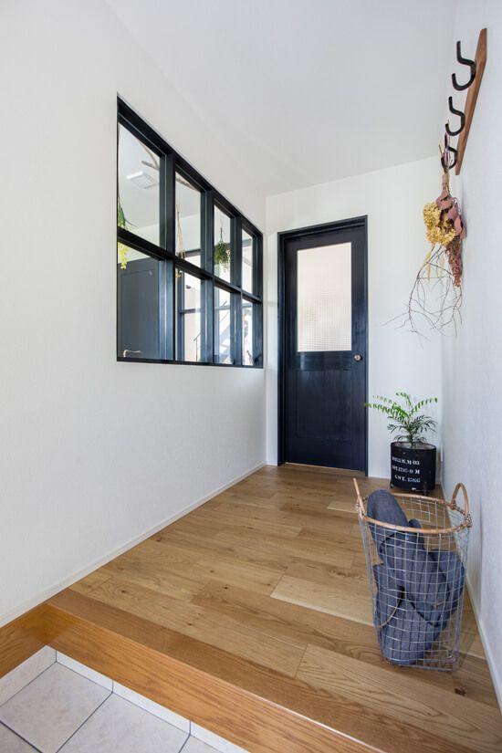 玄関入って正面の建具の色と室内窓の枠色をチャコール色で合わせて統一