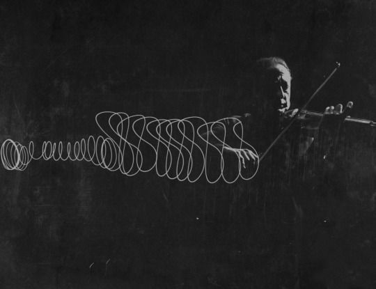 Gjon Mili,  Violinist Jascha Heifetz playing in Mili's darkened studio as light attached to his bow traces the bow movement, New York, 1952.
