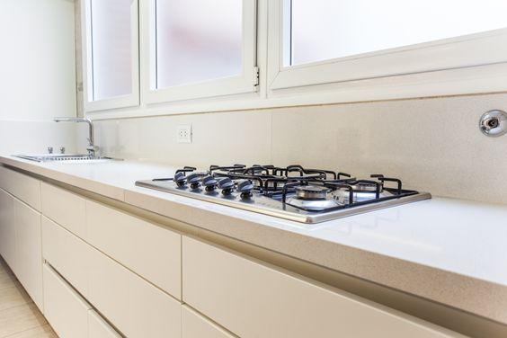 Cocina blanca, mesadas de silestone y muebles de pvc blanco. Modulación apaisada.