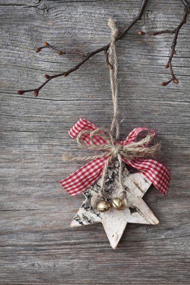 A una estrella realizada en madera, le puedes añadir unos cascabeles y un lazo realizado con tela en cuadros vichy y colgarla de una pequeña cuerdecita.