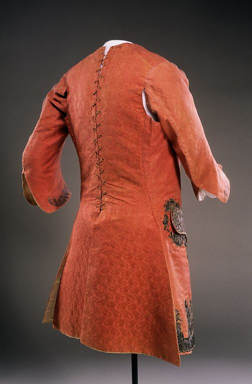 Rear view, sleeved waistcoat, fabric: England, garment: America, c. 1759. Flame-orange figured silk with an abstract feather/scroll and leaf design. The dense embroidery consists of silver metallic threads over stiffened paper scroll cut-outs, appliquéd onto the ground fabric, silver buillion embroidery, pailletes and flattened strips decorate the wooden buttons.