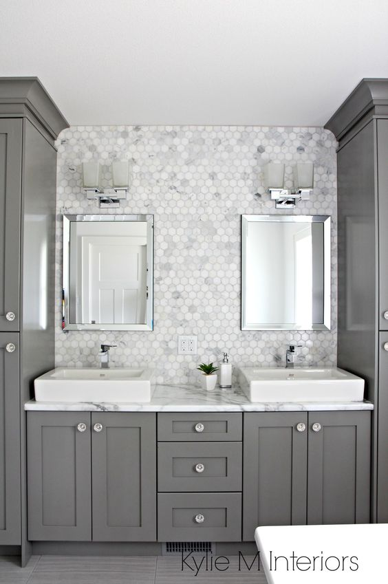 A bathroom with medium gray cabinets, gray and white tiles, mirrors and two vessel sinks