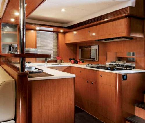 """The galley of the Swift 52 is fully equipped. The shelf over the counter at left is a great place to install extra cabinets if the chef doesn't mind being cut off from the saloon action. The steps at right have comfortable 7"""" (17.7 cm) risers and lead to the raised pilothouse."""