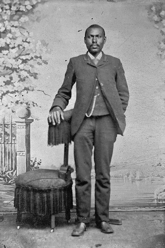 This gentleman's well tailored outfit highlights many of the fashions of the 1880's. Note the extremely narrow lapel on the sack coat, the high button front and the curved front of the jacket. His trousers are also tailored to a more slim style, note that there are still no creases in the front of his trousers as the press had not yet been invented. He wears his coat buttoned only at the top to proudly display his vest and watch chain.