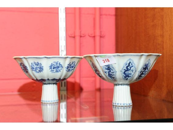 Two scallop rimmed, blue and white pedestal cups, one decorated with dragon and flaming pearl the other decorated with flowers, each with six character mark. 10cm high  Estimate: 1200-1500
