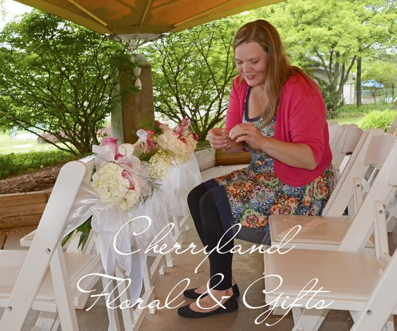 The owner of Cherryland Floral & Gifts puts the finishing touches on chair sashes at an elegant spring wedding in Traverse City, Michigan.