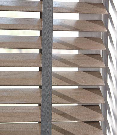 Maak gebruik van een contrasterende kleur ladderband van uw houten jaloezie om deze raamdecoratie een persoonlijk tintje te geven.