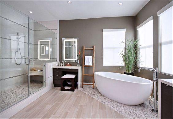 salle de bain moderne zen aménagée avec une cabine douche, une baignoire îlot blanche et mosaïque de sol aspect cailloux