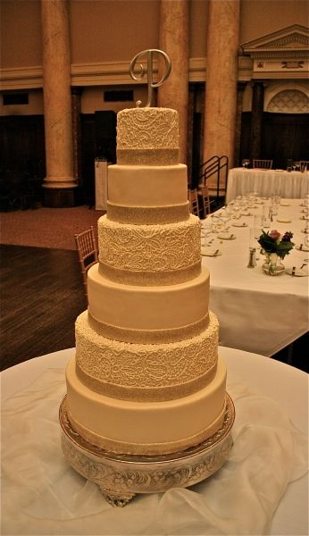 6 tier pearlized wedding cake with hand piped detail and edible glitter ribbon around each tier