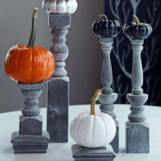 Create a Halloween centerpiece or room decoration by topping black pillars with miniature pumpkins.