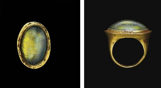 A GREEK GOLD AND GLASS FINGER RING   HELLENISTIC PERIOD, CIRCA 2ND-1ST CENTURY B.C.   The circular hoop flat on the interior, rounded on the exterior, expanding to the large, flaring two-stepped oval bezel, set with an oval green glass cabochon