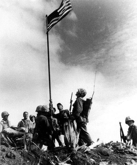 United States Marines from the 5th Division of the 28th Regiment gather around a U.S. flag they raised atop Mt. Suribachi on Iwo Jima during World War II, Feb. 23, 1945.  This was the first flag raised by the Marine Corps at Iwo Jima. The raising of a second, larger flag later that day was made famous in the prize-winning photo by Associated Press photographer Joe Rosenthal. (AP Photo/U.S. Marine Corp, Sgt. Louis R. Lowery, File) #