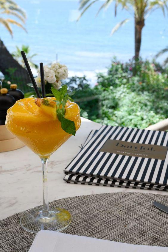 un cóctel de mango en una mesa del restaurante bardot, mirando al mar