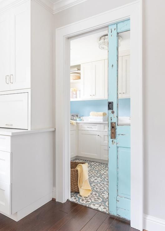 Charming Farmhouse Laundry Room With A Turquoise Blue Vintage Pocket Door Farmhouse Laundry Room Laundry Room Doors Laundry Room Decor