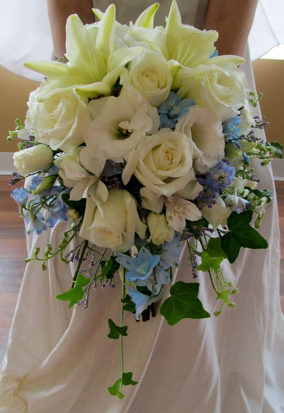 White lily, roses and lisianthus blooms accented with pale blue delphinium.