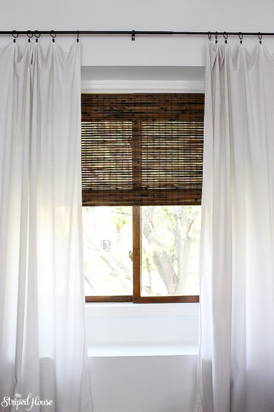 window makeover with bamboo blinds, white curtains and classic black curtain rod #traditionaldecor #interiordesign #homedecorideas #oneroomchallenge #myhousebeautiful #livingroom #decor #windowtreatment