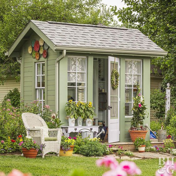 This cottage potting shed takes design cues from the main house, using the same earthy green and white paint colors. Extras like a deck, stone path, and cottage-style mixed planting borders make the backyard shed design feel more like a home than just an outbuilding. Several garden shed decorating ideas, like lace curtains in the windows, a quaint bench, and outdoor art also add homey appeal. In a practical move, downspouts ensure rains don't damage the pl #homeGarden