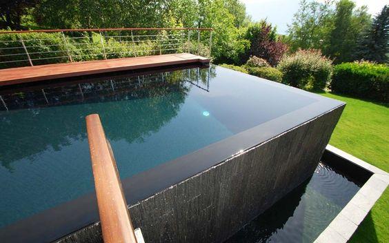 Exemple de piscine à débordement cascade dans une maison avec un jardin en pente