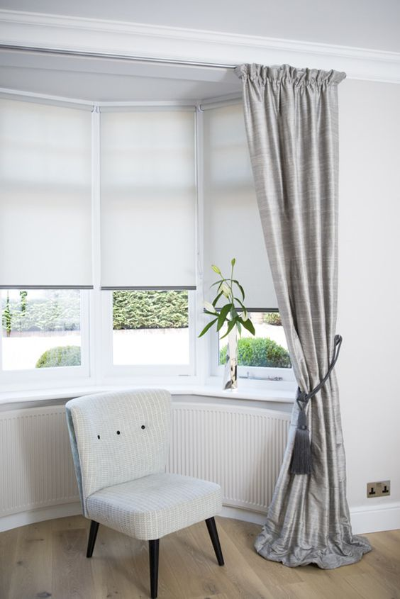Dressing a bay window by combining curtains and roller blinds creating a simple elegance: