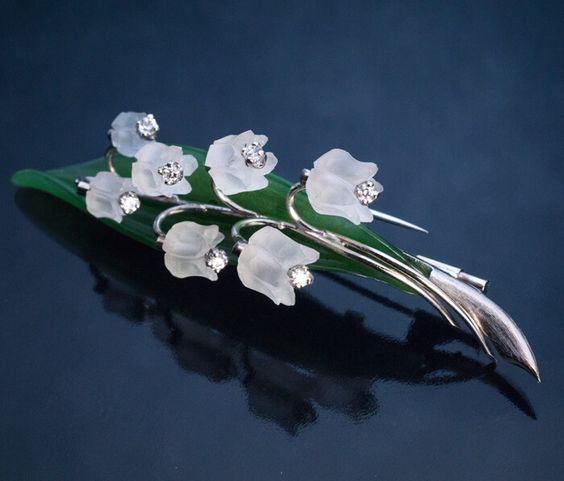 This large realistically modelled 3 - dimensional white 14K gold, hand carved nephrite jade and frosted rock crystal lily of the valley brooch / pin was ma