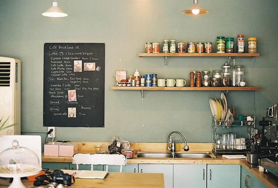 gorgeous colours in this kitchen. twin sink, wooden bench top, painted doors grey walls, chalk board, dish rack, coffee machine