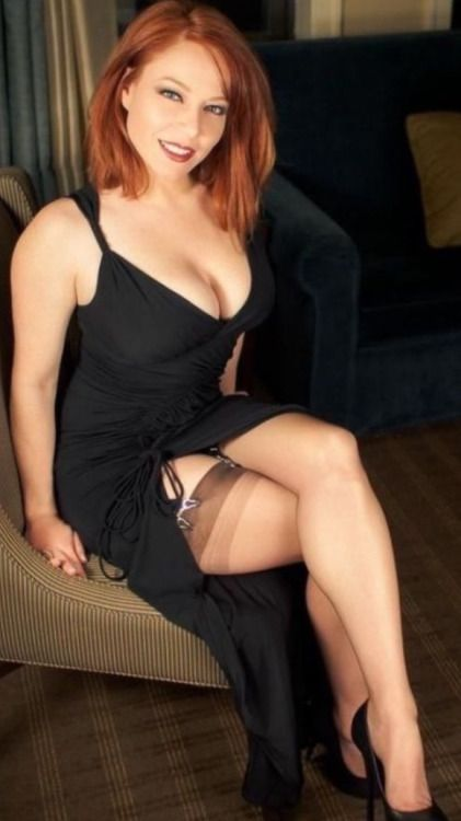 Sexy redhead wearing a tight fitted, long black dress.