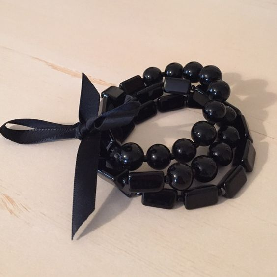 Set of Three Black Beaded Bracelet In excellent condition. Extremely elegant and eye-catching. Glossy black beads held together with a single ribbon. Jewelry Bracelets