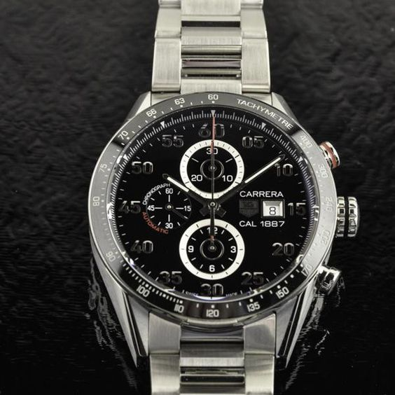 Pre-owned Tag Heuer Carrera Calibre 1887 43 mm watch crafted with a stainless steel case and bracelet and graced with a fixed black ceramic bezel and tachymeter. Includes a date display at the 3 o'clock position, chronograph- three subdials displaying: 60 second, 30 minute and 12 hour.