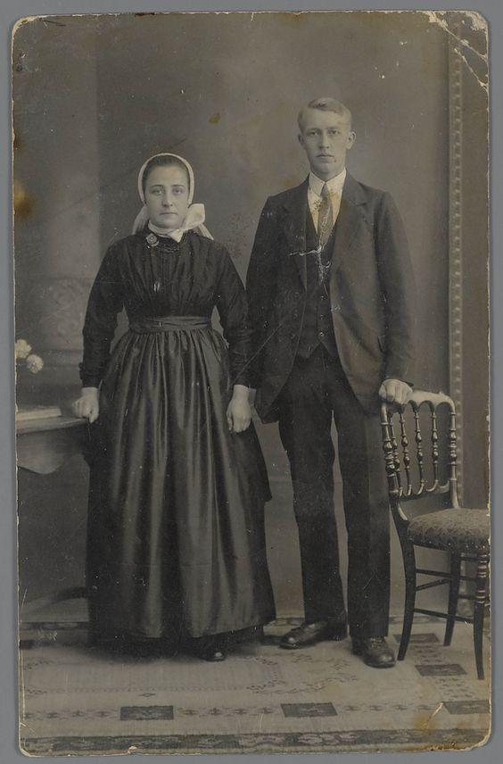 Trouwfoto uit 1922, van een echtpaar in Twentse streekdracht. Mogelijk zijn ze afkomstig uit de omgeving van Almelo. De vrouw draagt schootjak en rok met schort. Op het hoofd draagt ze een cornetmuts, om haar hals een 'knupdoekje' en kralensnoer met ronde sluiting. De man draagt een modekostuum. #Overijssel #Twente #Saksen