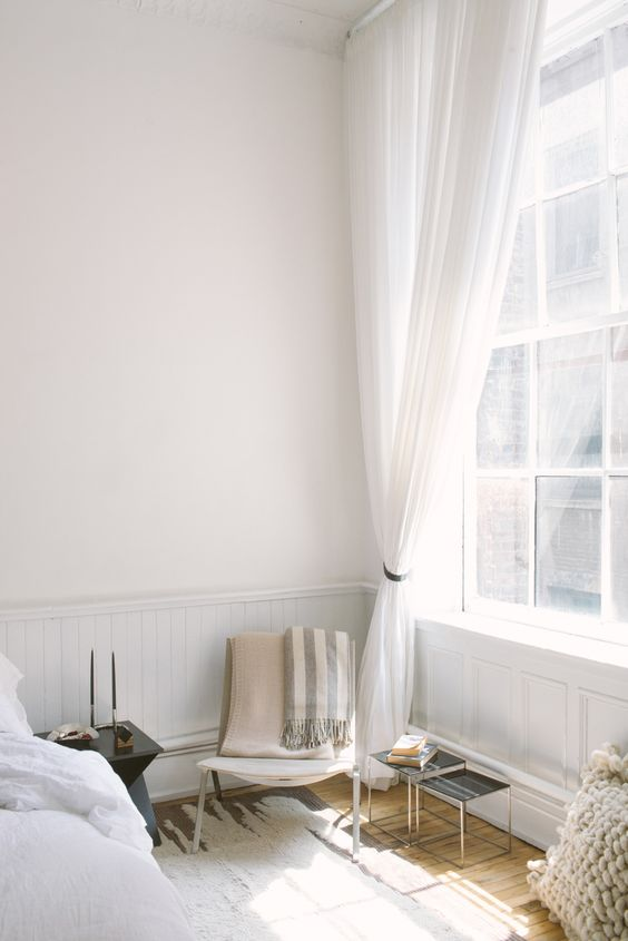 Gorgeous bedroom with sheer white curtains and natural light: