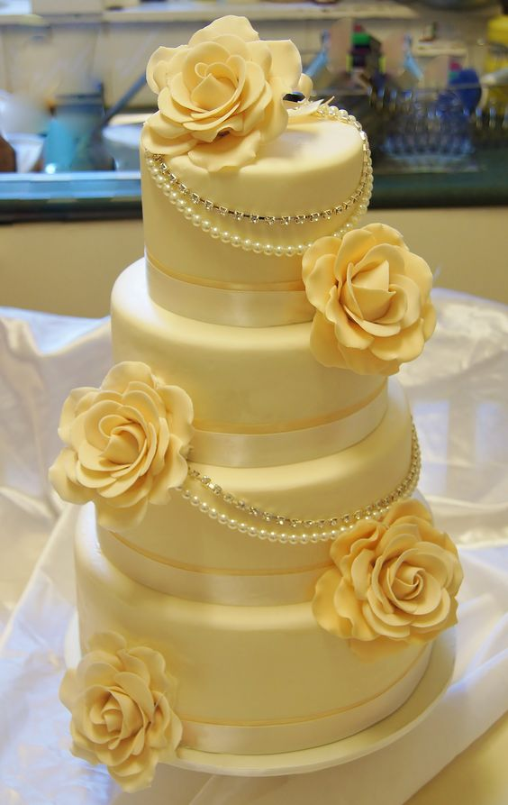 Gorgeous wedding cake with roses.  I love the draped pearls and the shade of yellow is just right.  Beautiful!  ᘡղbᘡ
