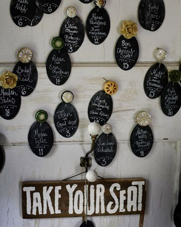 A vintage door displays escort cards fixed with an eclectic mix of knobs from Anthropologie