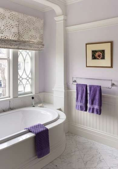 Beyond White: 11 Alternative Hues to Color Your Bath - Lavender - There are endless choices for nearly white paint colors that have a hint of another hue—like this ethereal lavender—making them a good option for anyone who just wants to turn up the volume of a white bath ever so slightly. A playful pattern on the Roman shade and towels in a deeper shade of purple add a bit of whimsy to the room.