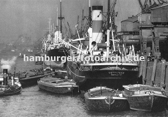 0953996 An der Kaianlage des Auguste Victoria Kais im Kaiser-Wilhelm-Hafen liegen Dampffrachter; Kräne löschen die Ladung oder beladen die Schiffe. Auf der Wasserseite der Frachtschiffe haben Schuten fest gemacht - sie werden über das bordeigenes Geschirr der Frachter beladen. Ganz links ein Schlepper, der eine Schute an ihre Position bringt. Links im Hintergrund die Stirnseite des Kaiser-Wilhelm-Hafens mit dem Reiherkai.