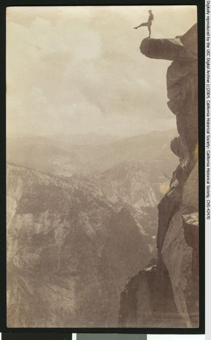 A man poses atop Overhanging Rock at Yosemite National Park's Glacier Point, circa 1920s.