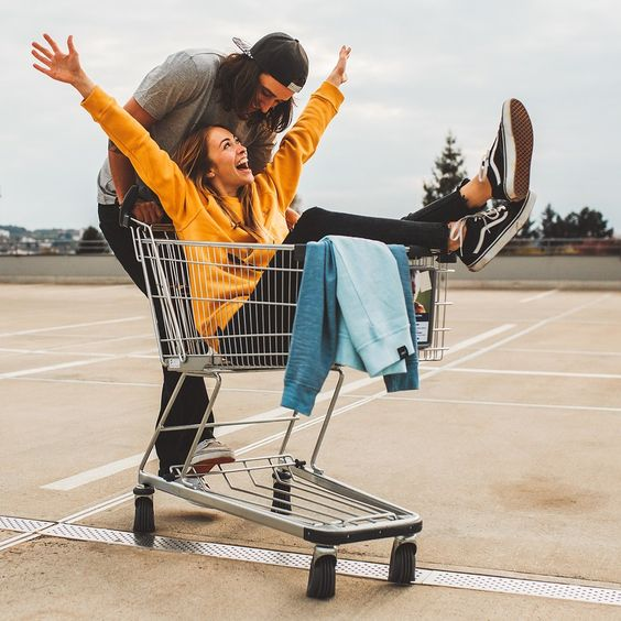 Goofing off in a shopping cart makes for a playful pic that shows off this couple's young at heart vibes.