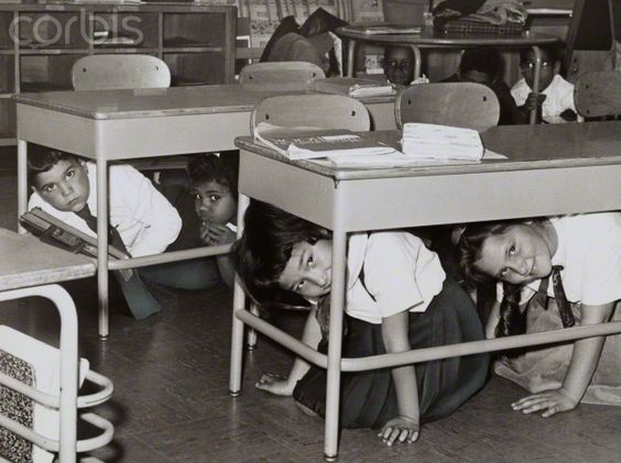 Students at a Brooklyn middle school have a 'duck and cover' practice drill in preparation for a nuclear attack; silver print, 1962.