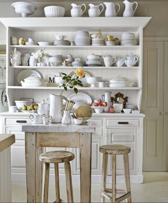 White dishes in a hutch in a kitchen with Paris inspired design by Myra Hoefer. #cottagestyle #whitekitchen #paris #openshelves