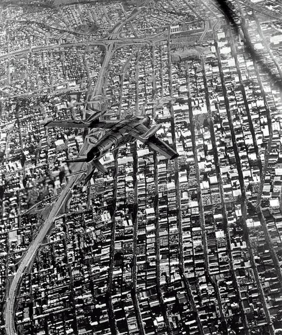 A jet fighter maneuvers high above downtown Los Angeles, 1954.
