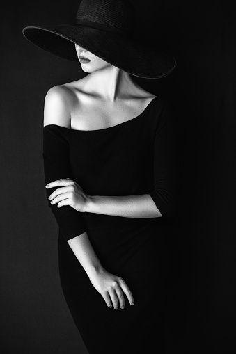 Studio shot of young beautiful woman wearing hat: