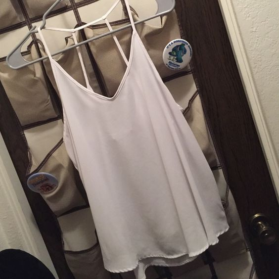 White tanktop Flowy white tanktop. The straps are very cute as seen in pictures. Only worn once and it has no holes or stains Lush Tops Tank Tops