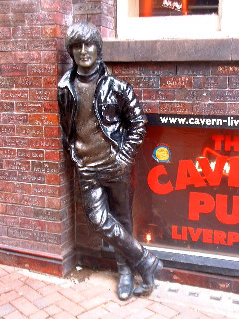 Liverpool Monuments: Beatles, John Lennon leaning against the wall of the building which stands where the Cavern Club used to, in Matthew Street. The wall behind the statue is engraved with the names of all the artistes who appeared at the Cavern